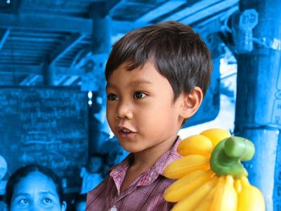 A child holds up plastic bananas during a class at a community pre-school in Sokang Commune, Kang Meas District, Cambodia, in June 2015.