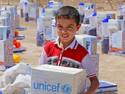 A boy picks up part of an emergency supply kit provided by UNICEF at a distribution in Diwaniyah, Iraq, in Augusto 2015.