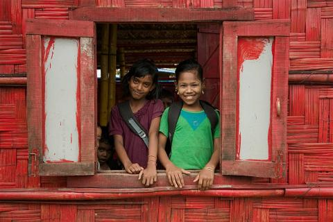 Two girls smiling from an open window
