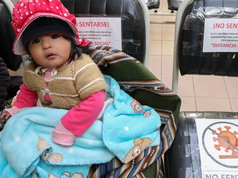 A baby, along with her mother, waits to be seen for a medical checkup at the Los Pinos health centre in the Senkata district of El Alto, Bolivia, in May 2020. Chairs in the waiting room are separated with signage to maintain social distancing as part of measures to stem the spread of COVID-19.