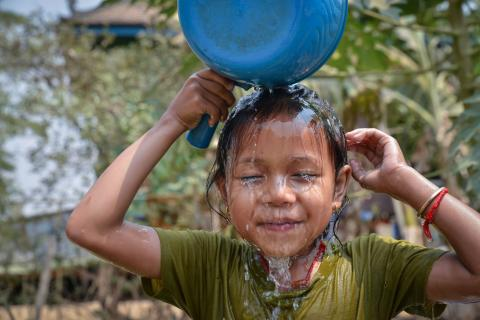 In Cambodia, Mara, 5, uses a cooking pot for her shower after school.