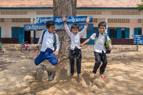 Three boys jumping up in front of a school