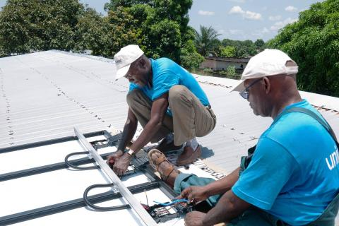 UNICEF staff on a rooftop installing solar refrigerators