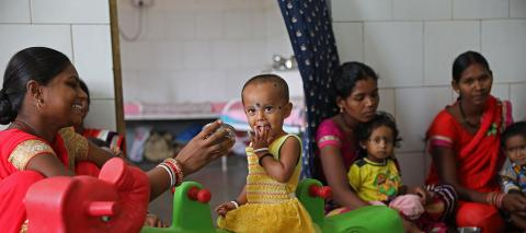 A toddler is fed by a woman during a meal at the Nutritional Rehabilitation Center at a district hospital in Rajnandgaon near Raipur, Chattisgarh, India, in April 2019.