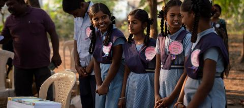A group of teenage girls stand and wait to receive soap at a SWAVOS meeting at Zilla Parishad High School Veldhi, India, February 2019.