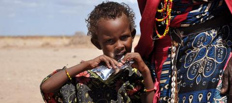 A 5-year old girl suffering from moderate acute malnutrition following the drought in Northern Kenya, opens one a sachet with ready-to-use therapeutic food (RUTF), in May 2017.