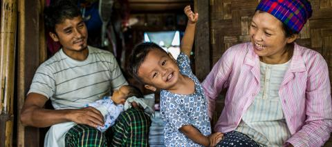 A couple and their two small children pictured sitting outside their family's shelter-room, at Maina IDP camp, Waingmaw, Kachin State, Myanmar, in July 2020.