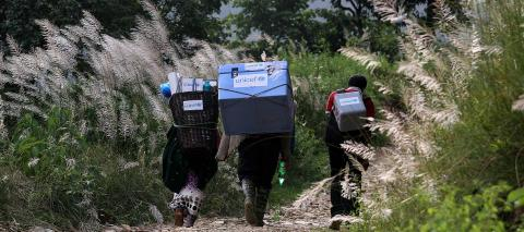 Three people carrying UNICEF-provided vaccines on difficult terrains on the way to a vaccination campaign to be conducted in Gorkha District, Nepal, the epicentre of the 2015 earthquake.