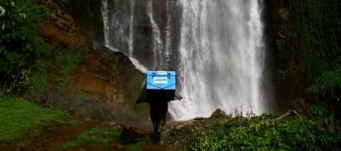 With a waterfall in the background, a porter carries UNICEF-provided vaccines on difficult terrains on the way to a vaccination campaign at the Barpak Village Development Committee (VDC) health post in Gorkha District, the epicentre of the earthquake in Nepal in 2015.