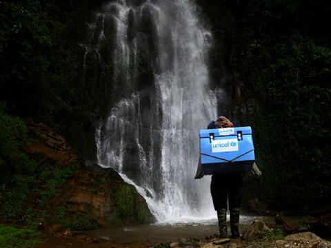 A porter carries UNICEF-provided vaccines on difficult terrains on the way to a measles, rubella and polio vaccination campaign to be conducted at Gorkha District, Nepal, the epicentre of 2015 earthquake.