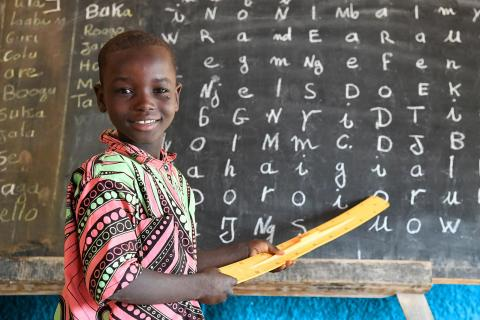 A boy stands in front of a blackboard in a school in Gourou Kirey, a suburb of Niamey, the capital of the Niger.