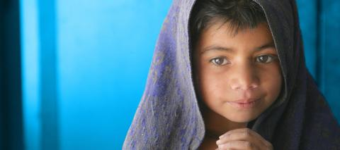 A girl wrapped in a blanket clasps her hands, at Model Primary School for Girls, in the village of Girani in Balochistan Province, Pakistan, in 2006.