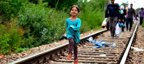 Refugee girl running on a train track.