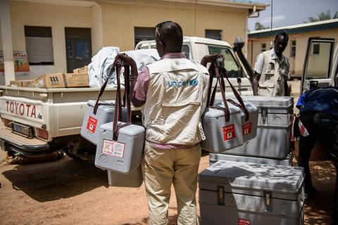 UNICEF health worker carries cold boxes containing vaccines to a pick-up truck ahead of a rural vaccination drive in Koch county, in Bentiu, South Sudan, May 2017.