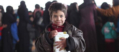 A child holds a box of high-energy biscuits distributed by UNICEF to children in a large warehouse in Jibreen, now used as a shelter for thousands of families who fled violence in east Aleppo, in December 2016.
