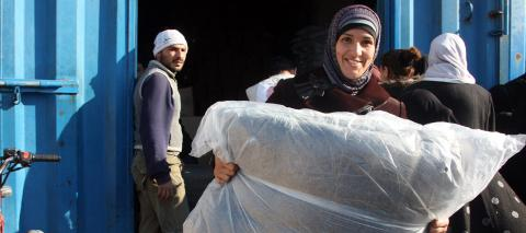 A smiling woman holds UNICEF blankets, among the five she just received during a distribution at a Syrian Arab Red Crescent warehouse, in the city of Lattakia, in December 2013.