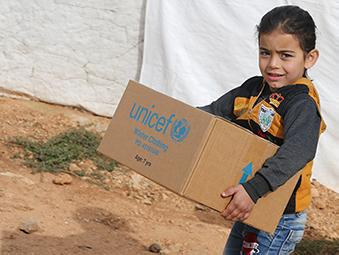 In the town of Ersal, East Lebanon, near the Syrian border, a girl walks with a box containing winter clothing provided by UNICEF in December 2018.