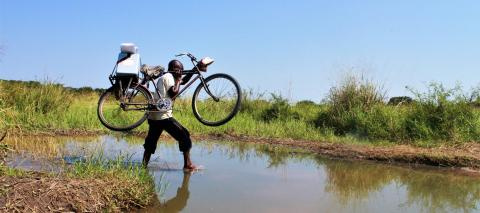 Permanent link toA community relay crosses a water stream with his bike to vaccinate children the most distant children in the health zone of Manono, Tanganyika Province, Democratic Republic of the Congo