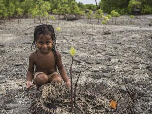 Teresa, 6, sits alongside a mangrove growing on top of dead coconut tree roots in the village of Tebunginako, Abaiang Atoll, South Tarawa, Kiribati, in 2016.