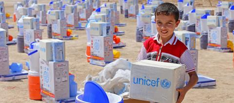 A displaced child stands among hundreds of emergency supply kits picking up one of them. The kits were distributed by the Rapid Response Mechanism (RRM) Consortium, led by UNICEF and WFP.