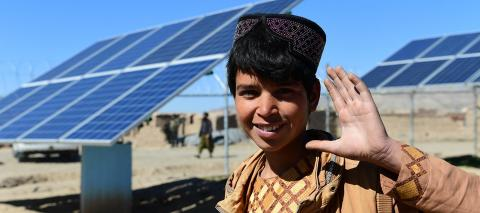 A boy waving his hand in front of solar panels that provide water in Herat, in the West of Afghanistan, in March 2020.