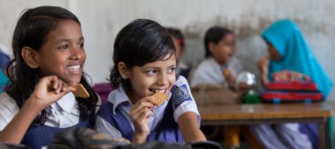 Two smiling schoolgirls of grade three enjoy protein-rich biscuits during their break period at Sher-E- Bangla Govenment Primary School, in Dhaka, Bangladesh, in October 2013.