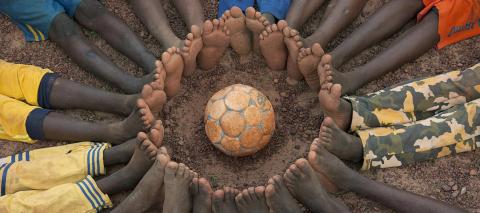 Circle of boys' bare feet with the soccer ball at a UNICEF Child-Friendly Space in Ouahigouya, Burkina Faso.