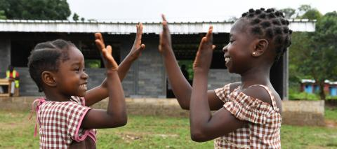 Two smiling girls play in front of their new school built with plastic bricks made out of recycled plastic, in Sangouine, a village in the West of Côte d'Ivoire.