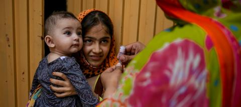 In 2017 in Khyber Pakhtunkhwa, Pakistan, a frontline health worker prepares to immunize a baby against polio in Shahin Muslim Town in Peshawar District.