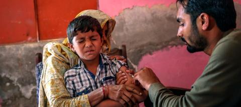 A trained vaccinator administers a Measles injection to six-year old Hasnain during the nationwide campaign in Bhojha village, Punjab province, Pakistan, in October 2016.