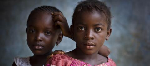 Two young girls pose for a photograph outside of their house in Tunkia, near to Kenema in Sierra Leone, in February 2016.