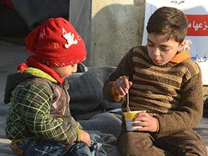 In December 2016, nearby Aleppo City, in Syria, a boy feeds his brother with therapeutic spread delivered by UNICEF to provide children with high energy and prevent malnutrition.