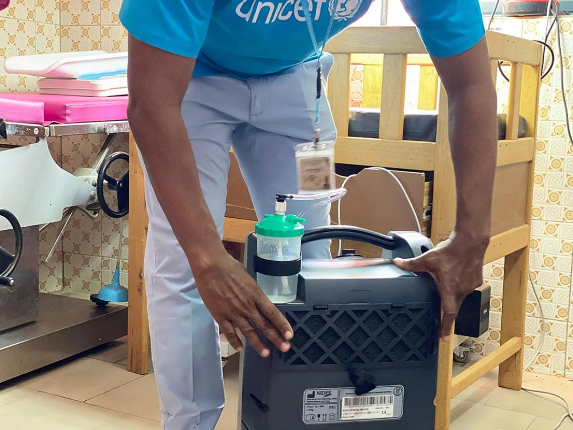A health worker adjusts an oxygen concentrator.