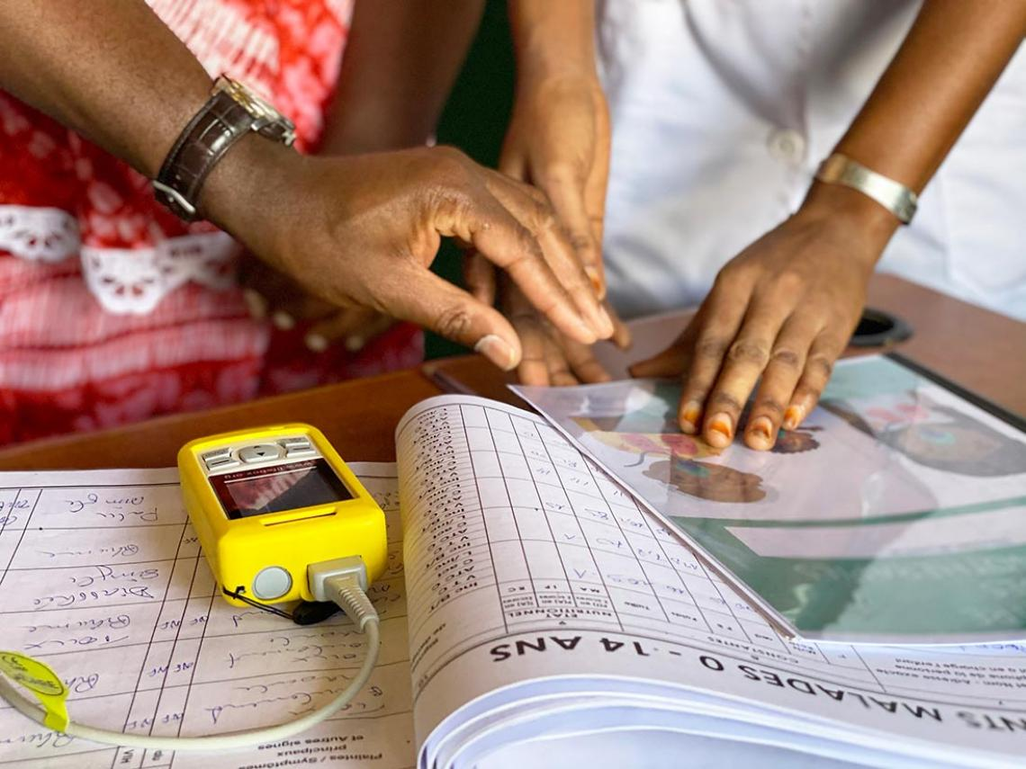 A pulse oximeter and hands of health workers discussing oxygen therapy.