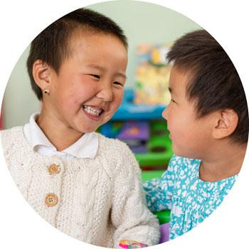 Two small girls smile to each other at an early childhood development center, supported by UNICEF, in Ulaanbaatar, Mongolia, in September 2018.
