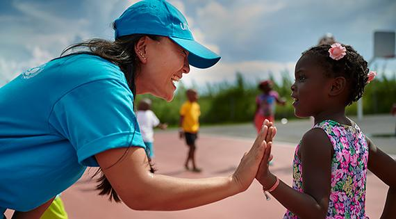 A woman wearing UNICEF t-shirt and cap greets a girl who was evacuated in the aftermath of Hurricane Dorian, in Bahamas, in September 2019.