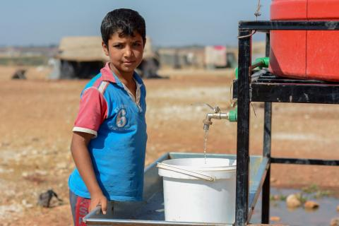 boy filling a water bucket with water from a tank