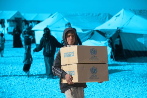 a boy holds a UNICEF assistance boxs