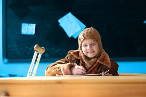 girl in classroom writing a letter