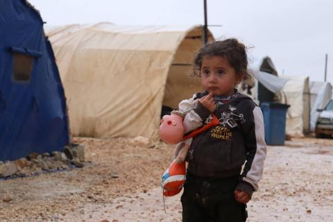 a child holding a dummy in a camp