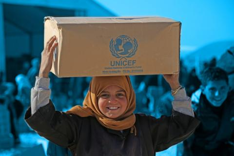 girl holding non food items UNICEF box