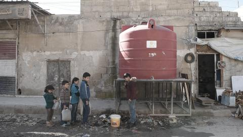 children waiting in raw to collect water from a water tank