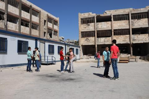 Children stand in the school yard in front of pre fabricated classrooms and damaged old school building