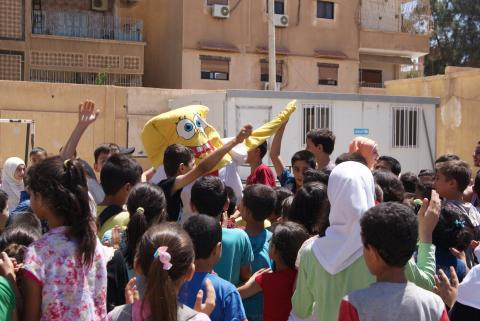 Children play with SpongeBob at a school
