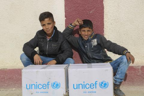 Two children sitting in front of UNICEF boxes
