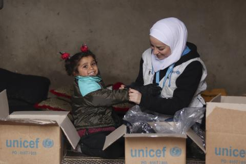 UNICEF staff helping a girl child to try a new Jacket