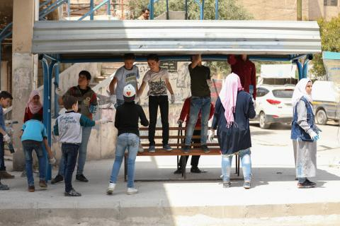 young children painting a bus stoop