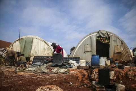 woman family checking belonging in front of tents