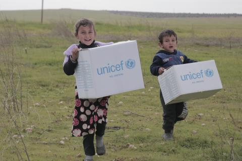 two children carrying UNICEF boxes