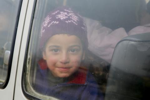 child looking out a car window